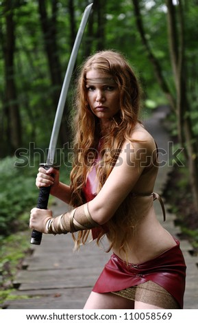 young woman with sword at forest - stock photo