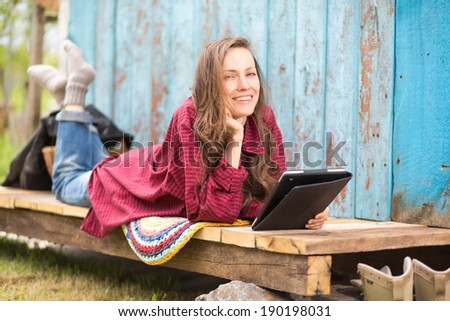 Young woman with tablet computer happy smiling while using digital device. soft daylight, copy space. focus on face - stock photo