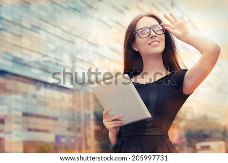 Young Woman with Tablet Out in the City - Woman wearing glasses, eyeglasses holding a PC tablet out in the city   - stock photo