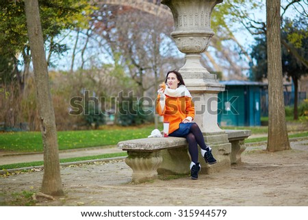 Young woman with take-away coffee and croissant near the Eiffel tower - stock photo