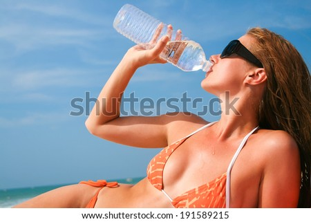 Young woman with tanned body drinking water - stock photo