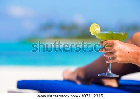 Young woman with tasty cocktail on beach loungers - stock photo