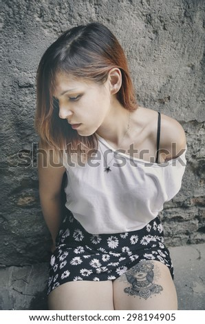 Young woman with tattoo on her leg - stock photo