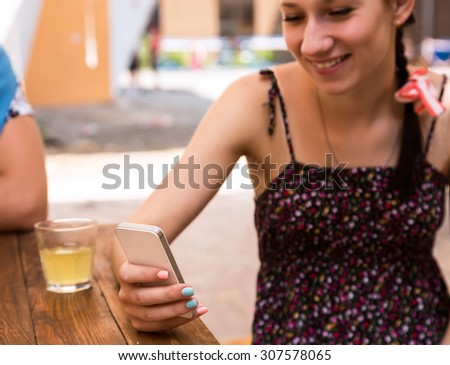 Young woman with telephone. Portrait of cheerful girl using white smart phone browsing internet colorful nail art summer leisure dress open street cafe desk drink glass outdoors - stock photo