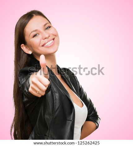 Young Woman with thumb up against a pink background - stock photo