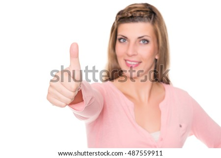 Young woman with thumbs up in front of white background