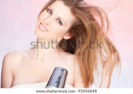 Young woman with towel holding blow dryer - stock photo