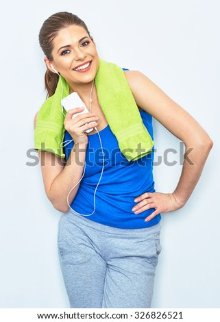 Young woman with towel on neck after exercise. Smiling girl listening music with smartphone. - stock photo