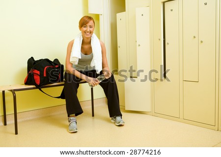Young woman with towel sitting on bench in locker room. She's holding bottle of water. - stock photo
