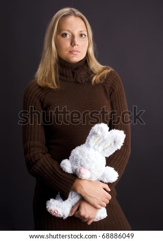 Young woman with toy bunny over black background - stock photo