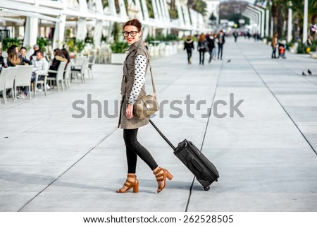 Young woman with travel bag and phone walking at the promenade in Split cty in Croatia - stock photo