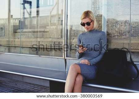 Young woman with trendy look reading information on mobile phone while waiting outdoors on a her taxi, stylish female tourist using cell telephone for view city map on-line while sitting on a bus stop - stock photo