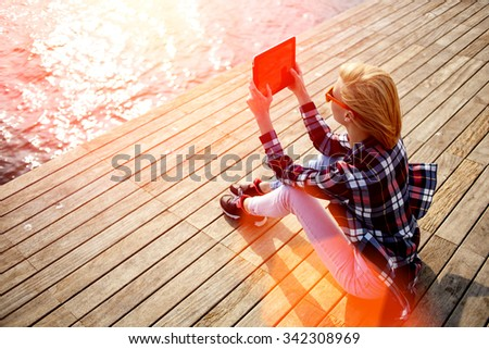 Young woman with trendy look shoot video on digital tablet while sitting on a wooden pier in summer sunny day, female hipster photographing on touch pad amazing landscape during her vacation holidays  - stock photo