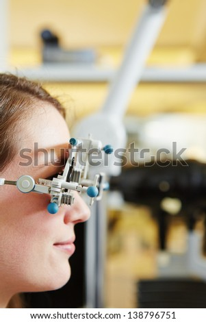 Young woman with trial frame for lens determination at optician - stock photo