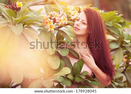young woman with tropical flower Plumeria alba - stock photo