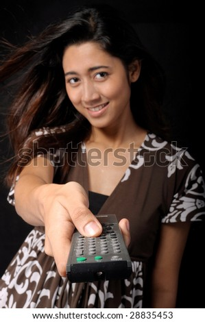 Young woman with TV remote control (focus on remote control). - stock photo