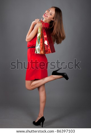 young woman with two bag on a grey bg - stock photo