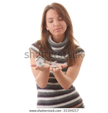 Young woman with two hose models in hands (compering them) isolated on white background - Real Estate loans concept - stock photo