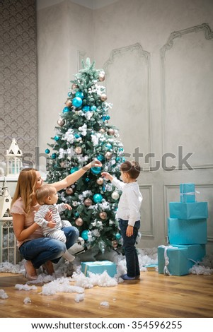 Young woman with two sons decorating on Christmas tree at home - stock photo