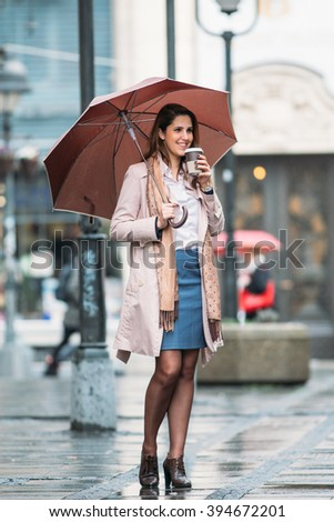 Young woman with umbrella at the street, drinking coffee and talking on the phone