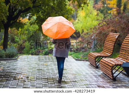Young woman with umbrella in beautiful autumn park. - stock photo