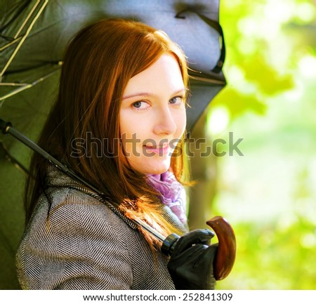 Young woman with umbrella in spring garden. - stock photo