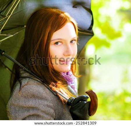 Young woman with umbrella in spring garden. - stock photo