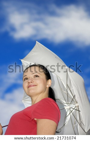 Young woman with umbrella over the blue sky - stock photo