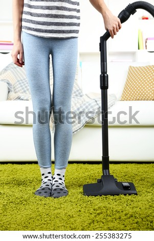 Young woman with vacuum cleaner in room - stock photo