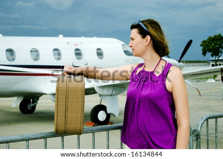 Young woman with valise around airplane