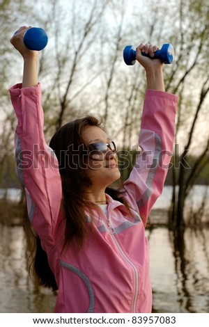 Young woman with weights exercising in the nature Healthy lifestyle and fitness concept - stock photo