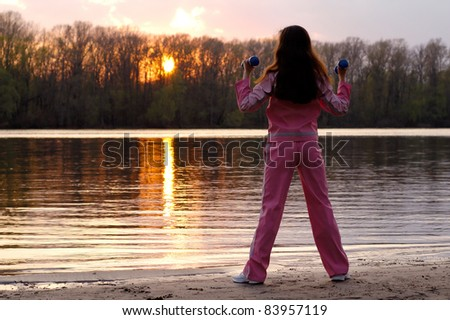 Young woman with weights exercising in the nature in sunset near the river Healthy lifestyle and fitness concept - stock photo