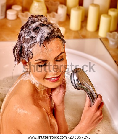 Young woman with wet head take bubble  bath. - stock photo