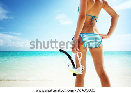 Young woman with wet skin and with a snorkel standing on sand and going to swim in clear sea - stock photo