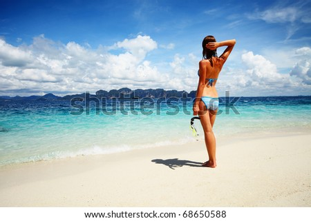 Young woman with wet skin going to snorkeling in clear sea - stock photo