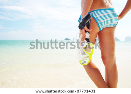 Young woman with wet skin standing on a sand and holding a mask and snorkel - stock photo