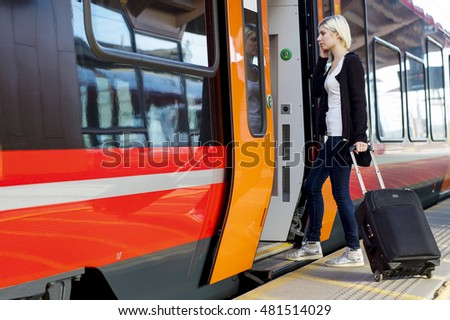 Young Woman With Wheeled Luggage Boarding Train