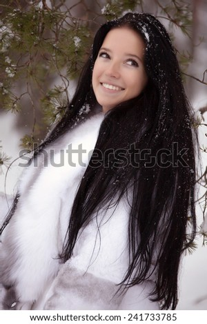 young woman with white fur coat in winter forest  - stock photo
