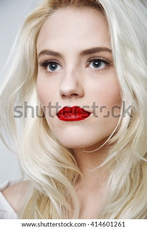 young woman with white hair and red lips - studio shot