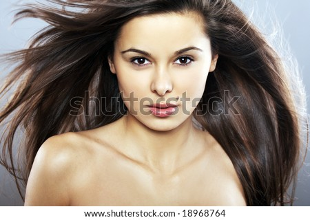 Young Woman with Windswept Hair on blue background - stock photo