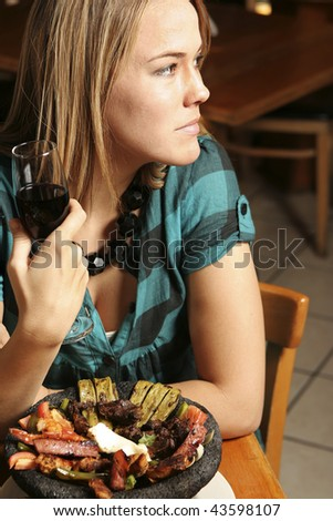 Young woman with wine gazing out of a restaurant window. - stock photo