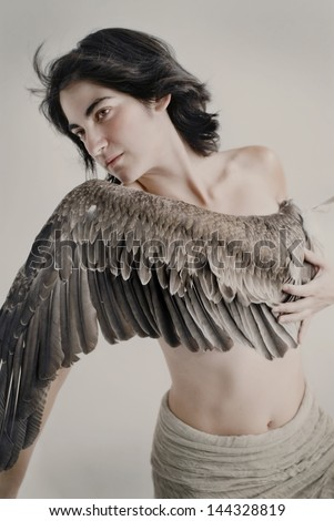 Young woman with wing across her chest. - stock photo