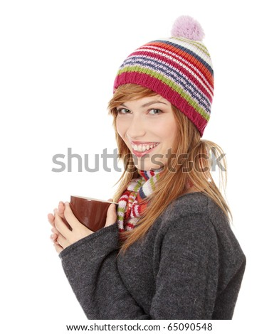 Young woman with winter cap drinking something hot, isolated on white - stock photo