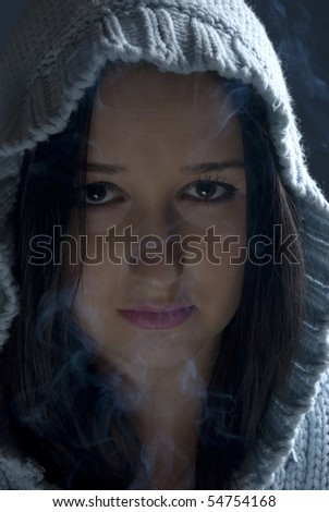 Young woman with wool hood in darkness with smoke around her