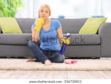 Young woman with yellow cleaning gloves holding a spray bottle and sitting in front of a gray sofa at home shot with tilt and shift lens - stock photo