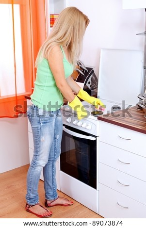 Young woman with yellow gloves cleaning the oven