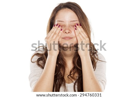 young woman without make-up rubbing her face