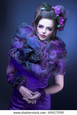Young woman witn bright make-up and with flowers in her hair
