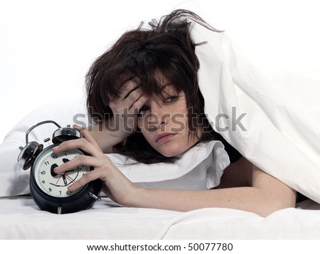 young woman woman in bed awakening tired holding alarm clock on white background - stock photo