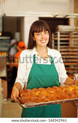 Young woman working at bakery - stock photo